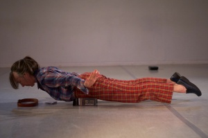 Linda Austin lying prone, belly on cassete boxes, a few inches off the ground