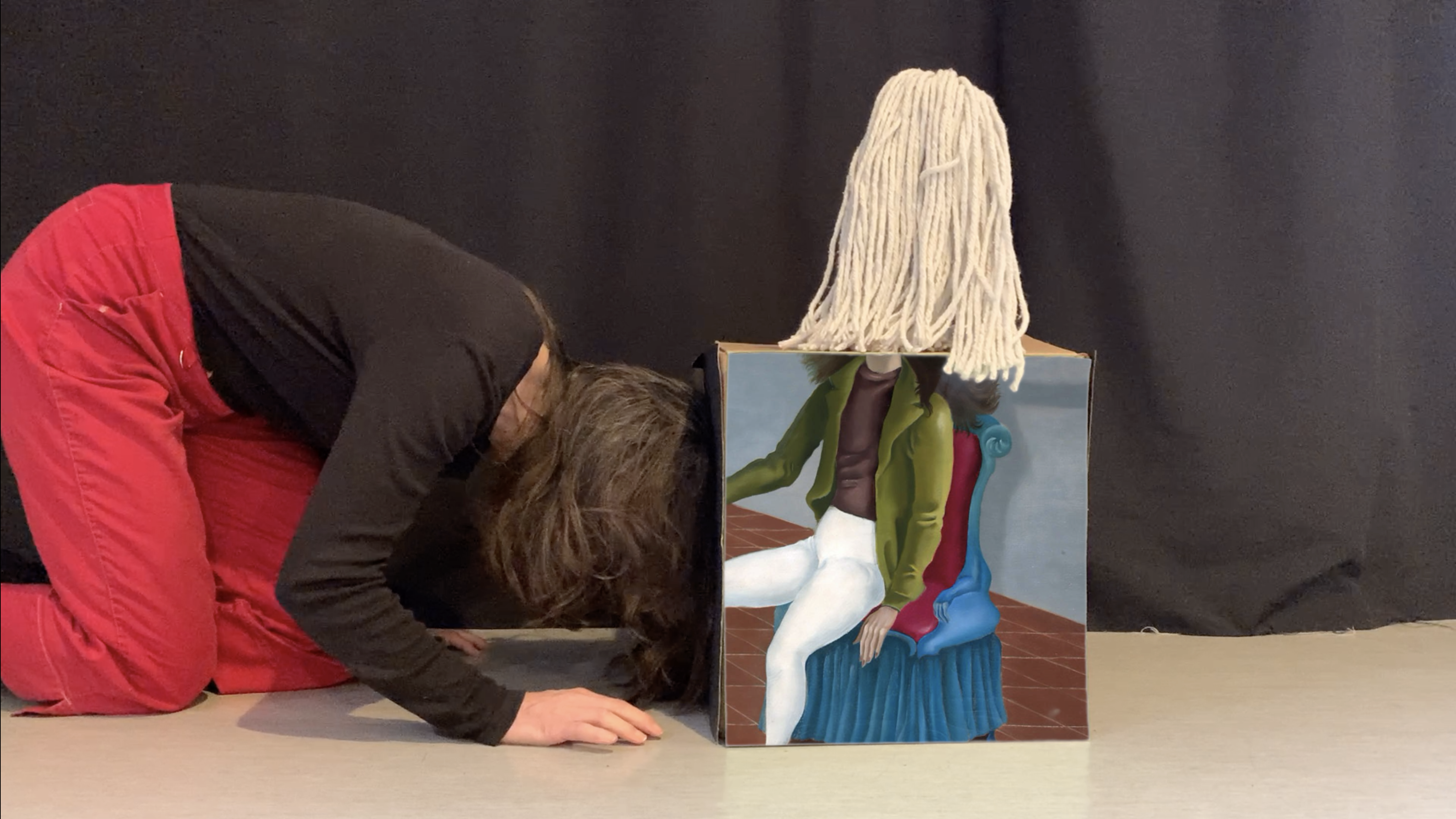 Person in red pants crawling and pushing a box with their head. The front of the box has an image of someone in white pants and green jacket sitting on a blue chair. Their head is above the frame of the image. The head of a string mop is on top of the box, sort of where the head of the person in the picture would be.